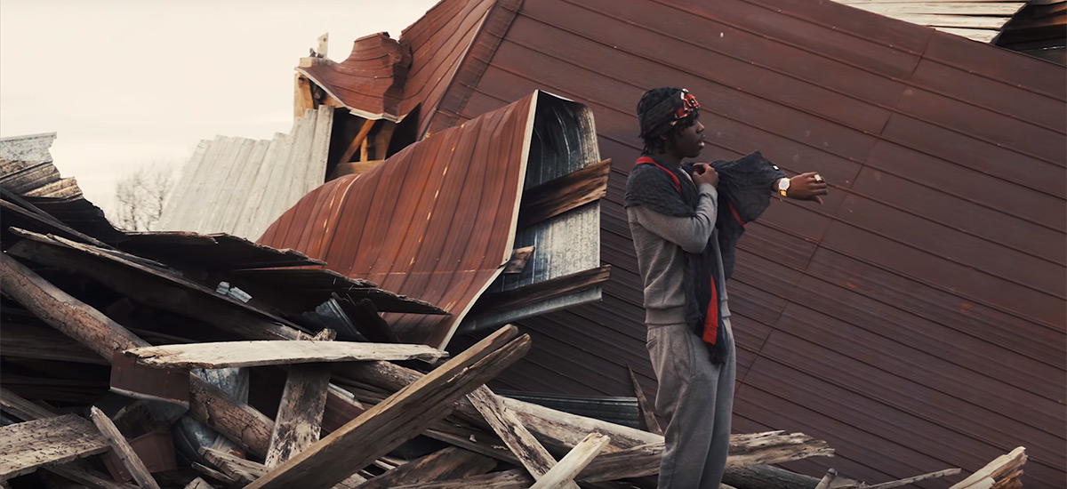 Toronto rapper Burna Bandz checks his gold watch in front of a torn down barn in Beast Mode.