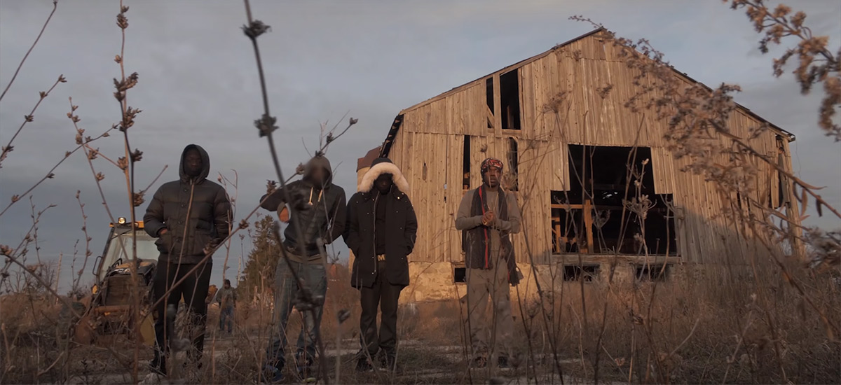 Burna Bandz and his crew outside of an abandoned barn in the Beast Mode video.
