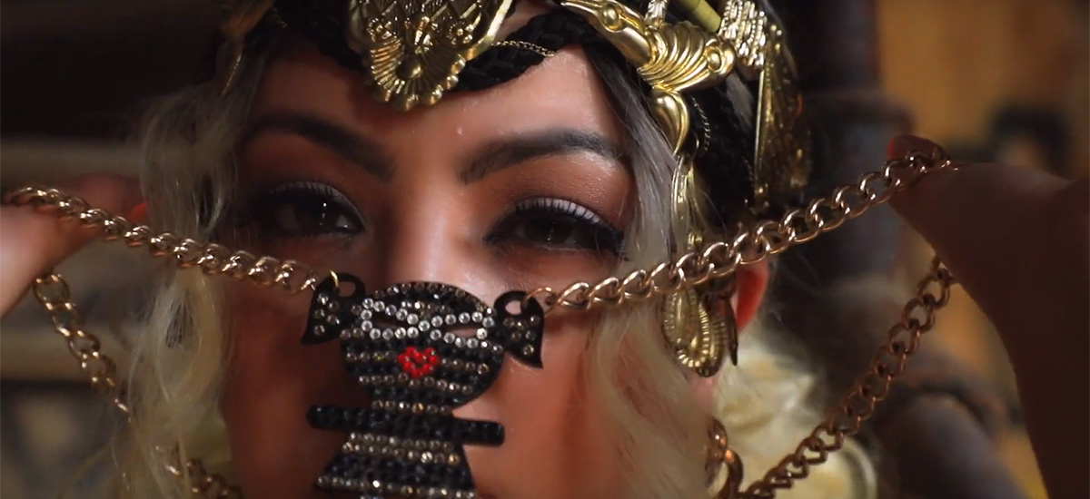 A closeup of Bronx rapper Mala Reignz holding up her chain, a screenshot from her Greener Side music video