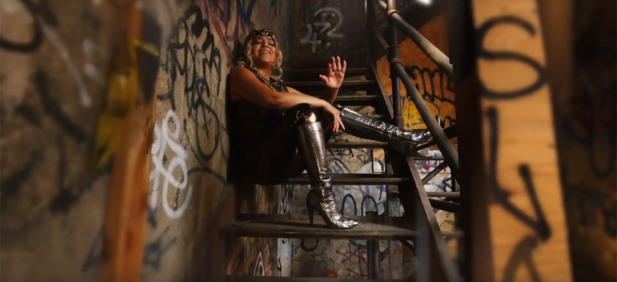A scene from the new Mala Reignz video Greener Side depicting Mala sitting on stairs spitting her lyrics.