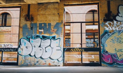 A scene from the Mala Reignz video Greener Side which shows an empty warehouse with graffiti on the wall.