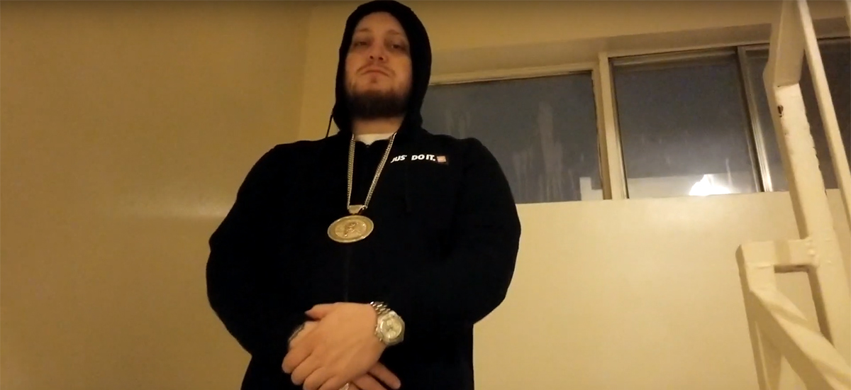 Project Prezzy, wearing a black hoodie with a gold chain, stands looking at the camera in the new Work Music video.