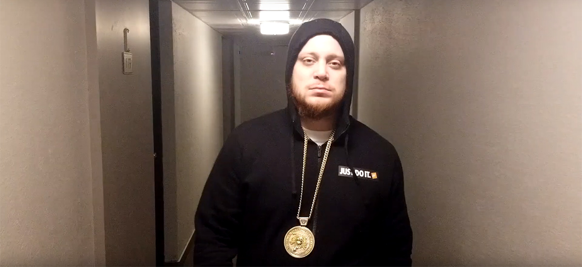 Project Prezzy, wearing a black hoodie with a gold chain, walks down the hall of an apartment building while looking at the camera in the new Work Music video.