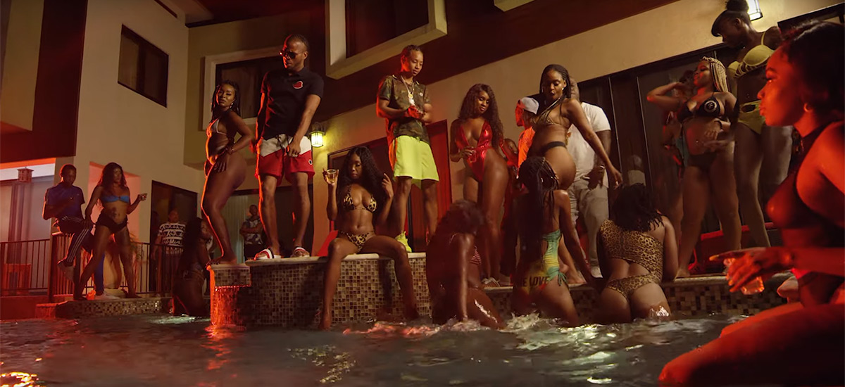 Screenshot from the new Big Accident music video by Pressa and Dexta Daps. The 2 artists are seen partying with a group of women around a pool.