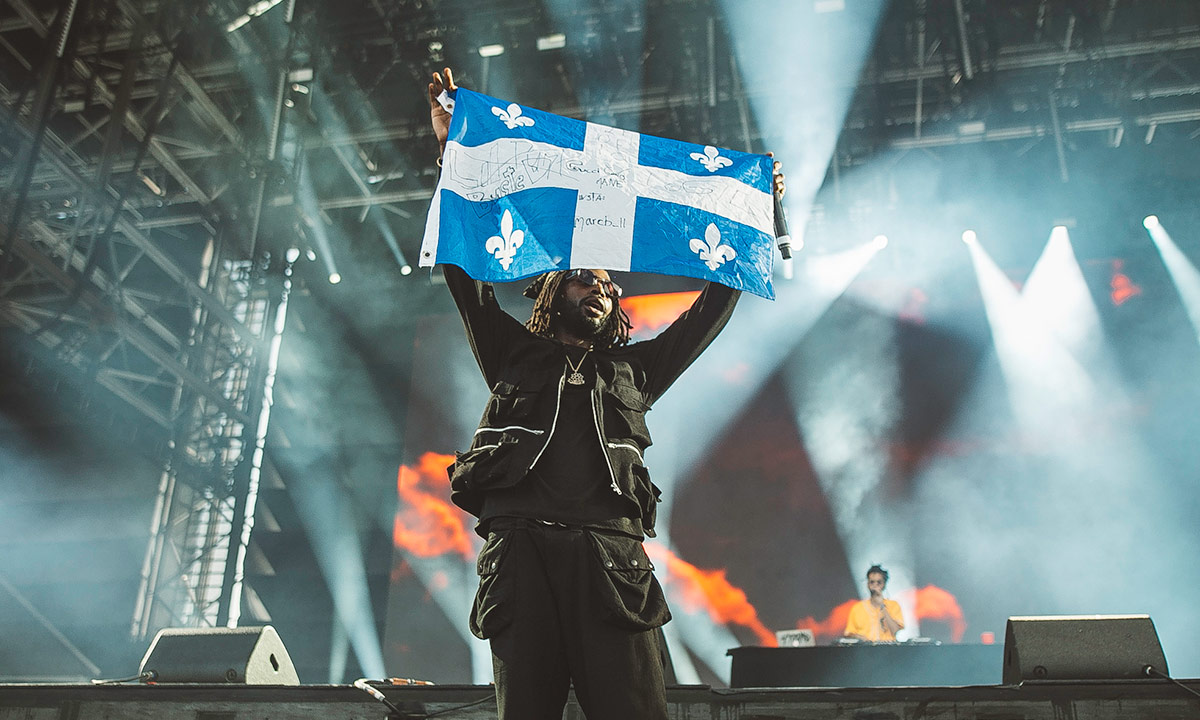 Rapper Jazz Cartier holds up a Quebec flag during his performance on Day 1 of FEQ 2019