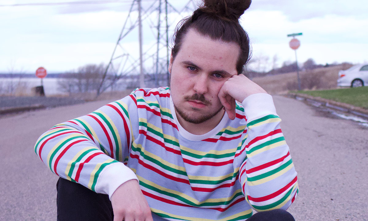 Nova scotian rapper Nomad Quinn in a red stripped white sweater, sitting on the road, resting his head against his hand.