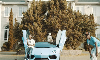 A scene from the new Burna Bandz video for CROS. Burna can be seen rapping his verse next to a luxury car.