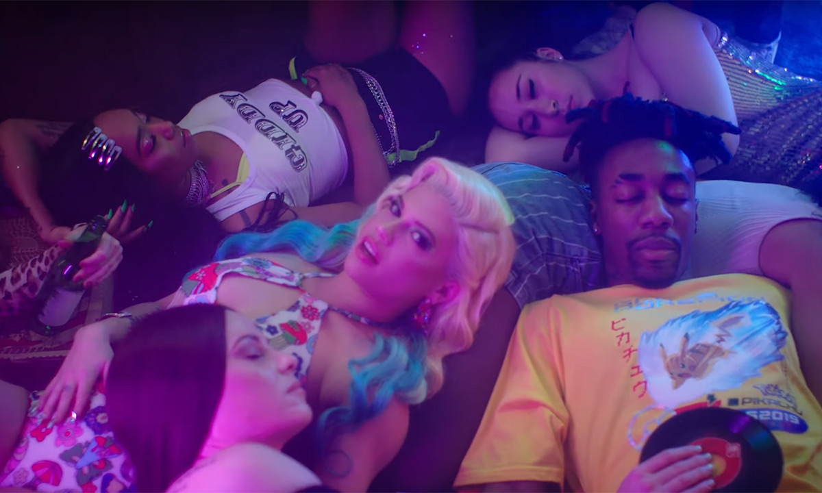Chanel West Coast and Dax in the new I Be Like video. Both artists are laying on the ground next to several other people who appear to be asleep. Dax has his eyes closed.