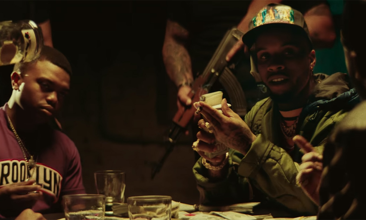 Tory Lanez is wearing a hat, seated at a table playing cards and holding a stack of money in his new video for Forever