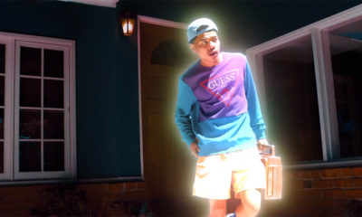 Budding star Bblasian in his new video for Upper Hand. He is wearing a purple and blue shirt, a backwards blue hat, and holding a boombox.