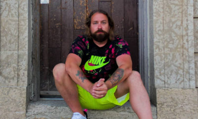 Canadian rapper Fortunato sits on a stoop wearing a black Nike shirt with a fluorescent logo, and matching fluorescent coloured shorts.
