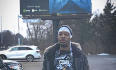 Mezziah standing in front of a Blue Aura billboard advertisement
