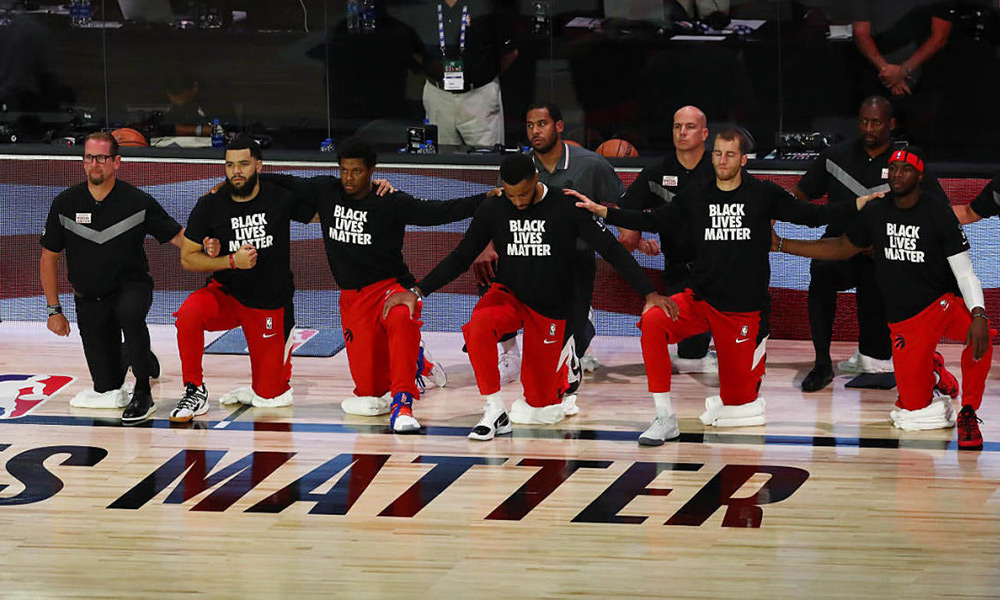 The Raptors kneel for the national anthems before Game 4 against the Brooklyn Nets